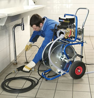 A Tempse Drain Clearing Specialist Uses a Power Auger to Clear a Laundry Room Drain
